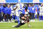 Tampa Bay Buccaneers quarterback Tom Brady (12) slides under Los Angeles Rams cornerback Jalen Ramsey (5) during the second half of an NFL football game Sunday, Sept. 26, 2021, in Inglewood, Calif. (AP Photo/Jae C. Hong )