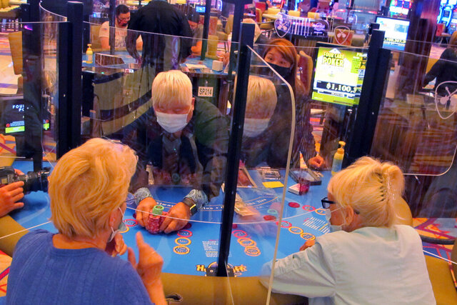 See-through barriers separate gamblers and a dealer at a card table at the Hard Rock casino in Atlantic City, N.J., on July 2, 2020, the first day it reopened after being closed for four months due to the coronavirus outbreak. American Gaming Association President Bill Miller said Tuesday, Oct. 27, 2020, the industry is adapting to the pandemic but needs assistance from the government for its casinos and workers. (AP Photo/Wayne Parry)