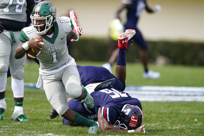 Mississippi Valley State quarterback Jalani Eason (1) escapes a sack attempt by Jackson State Justin Ragin (76) during the first half of an NCAA college football game, Sunday, March 14, 2021, in Jackson, Miss. (AP Photo/Rogelio V. Solis)