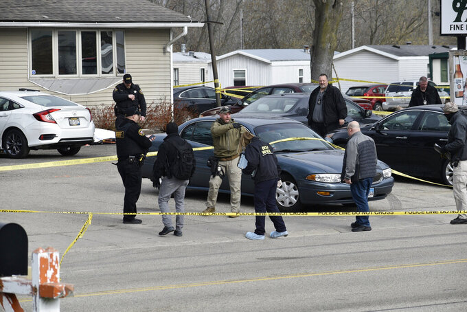 Investigators confer during an investigation outside the Somers House Tavern, in Kenosha, Wis., Sunday morning, April 18, 2021. Authorities say several people were killed and a few were seriously wounded in a shooting early Sunday at the tavern in Kenosha County in southeastern Wisconsin.  (Deneen Smith/The Kenosha News via AP)