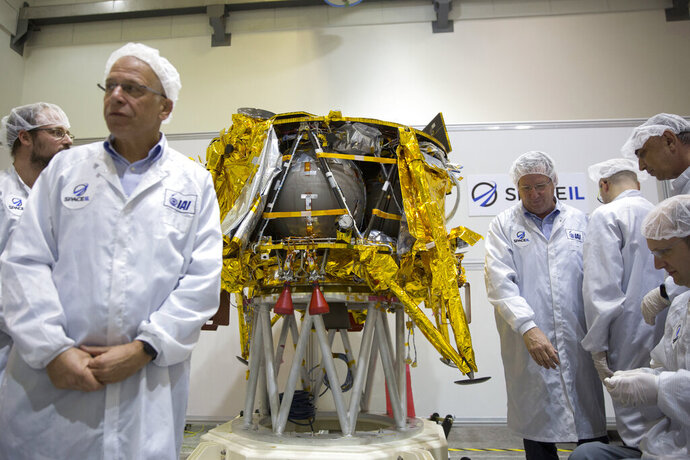 FILE - In this Monday, Dec. 17, 2018 file photo, technicians stand next to the SpaceIL lunar module, an unmanned spacecraft, on display in a special clean room during a press tour of their facility near Tel Aviv, Israel. SpaceIL and the state-owned Israel Aerospace Industries plan to launch the lunar lander on a SpaceX Falcon rocket Thursday night, Feb. 21, 2019, from Cape Canaveral, Fla. (AP Photo/Ariel Schalit)