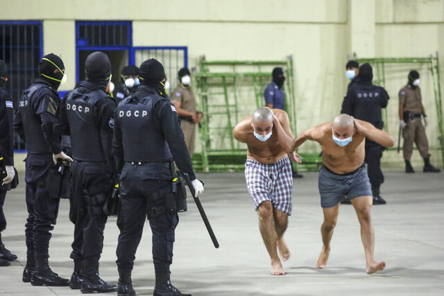 In this photo released by El Salvador Presidency Press Office police wearing masks as precautions against the new coronavirus guard inmates, also wearing masks, during a security operation after President Nayib Bukele decreed maximum emergency in prisons housing gang members at the Izalco prison in San Salvador, El Salvador, Saturday, April 25, 2020. Bukele ordered the emergency the day after more than twenty people were killed throughout country that authorities said were ordered from prisons. (El Salvador President Press Office via AP)