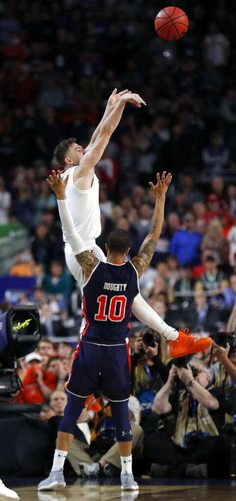FILE - In this April 6, 2019, file photo, Virginia's Kyle Guy shoots as he was fouled by Auburn's Samir Doughty (10) during the second half in the semifinals of the Final Four NCAA college basketball tournament, in Minneapolis. Guy sank all three free throws and Virginia defeated Auburn 63-62. (AP Photo/Charlie Neibergall, File)