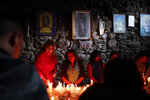 In this picture taken Monday, Jan. 6, 2020, people light candles inside the San Francisco Church during a Catholic Mass for Three Kings Day in La Paz, Bolivia. Outside the church, many parishioners flocked to indigenous guides to get additional blessings that come from the ancestral indigenous beliefs in the Pachamama, or mother earth deity. (AP Photo/Natacha Pisarenko)