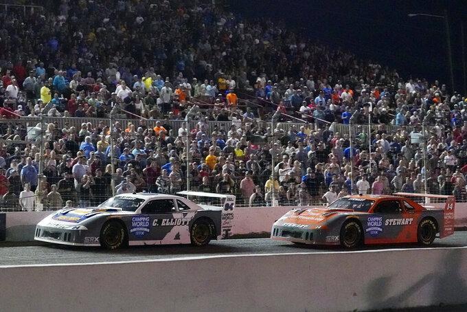 Chase Elliott (94) leads Tony Stewart during the SRX Series auto race Saturday, July 17, 2021, in Nashville, Tenn. (AP Photo/Mark Humphrey)