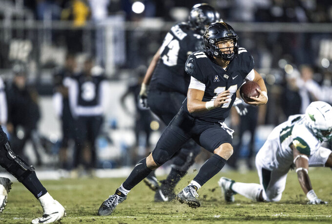 Central Florida quarterback Dillon Gabriel (11) runs out of the pocket during the second half of the team's NCAA college football game against South Florida, Friday, Nov. 29, 2019, in Orlando, Fla. (AP Photo/Willie J. Allen Jr.)