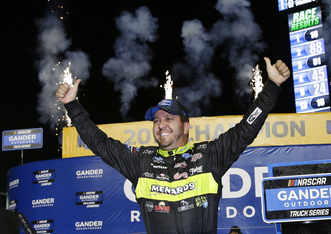 Matt Crafton celebrates in Victory Lane after winning the NASCAR Truck Series auto racing season championship, Friday, Nov. 15, 2019, at Homestead-Miami Speedway in Homestead, Fla. (AP Photo/Terry Renna)
