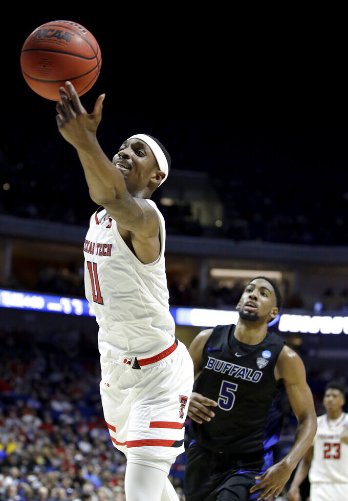 Texas Tech's Tariq Owens (11) and Buffalo's CJ Massinburg (5) chase a loose ball during the second half of a second round men's college basketball game in the NCAA Tournament Sunday, March 24, 2019, in Tulsa, Okla. Texas Tech won 78-58. (AP Photo/Charlie Riedel)