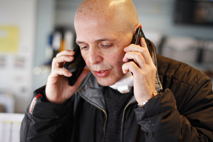 Pat Marmo, owner of Daniel J. Schaefer Funeral Home, speaks on two phones at once in his office while handling the overflow of clients stemming from COVID-19 deaths, Thursday, April 2, 2020, in the Brooklyn borough of New York. His office phone and two mobiles are ringing constantly. He's apologizing to families at the start of every conversation for being unusually terse and insensitive, and begging them to insist hospitals hold their loved ones as long as possible. (AP Photo/John Minchillo)