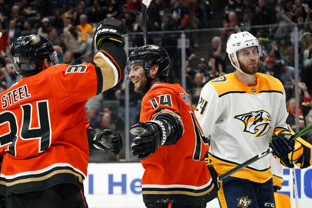 Anaheim Ducks center Adam Henrique, middle, celebrates with center Sam Steel, left, after scoring, as Nashville Predators defenseman Jarred Tinordi skates by during the second period of an NHL hockey game in Anaheim, Calif., Sunday, Jan. 5, 2020. (AP Photo/Chris Carlson)