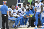 "FILE - In this Sunday, Oct. 18, 2020, file photo, Detroit Lions strong safety Duron Harmon (26), cornerback Darryl Roberts (29) and safety Jayron Kearse (42) review plays with defensive backs coach Steve Gregory and defensive coordinator Cory Undlin, right, on the sideline during the second half of an NFL football game against the Jacksonville Jaguars in Jacksonville, Fla. The NFL is recommending that players on the sidelines who are not participating in a game or about to go on the field wear protective masks, according to a league management council memo obtained by The Associated Press on Friday, Oct. 30, 2020. Although the NFL stopped short of mandating masks for all players not on the field, it ""strongly encouraged"" all active players in the bench area who are not about to enter the game to wear masks while standing on the sideline and/or sitting on the bench. (AP Photo/Phelan M. Ebenhack, File)"