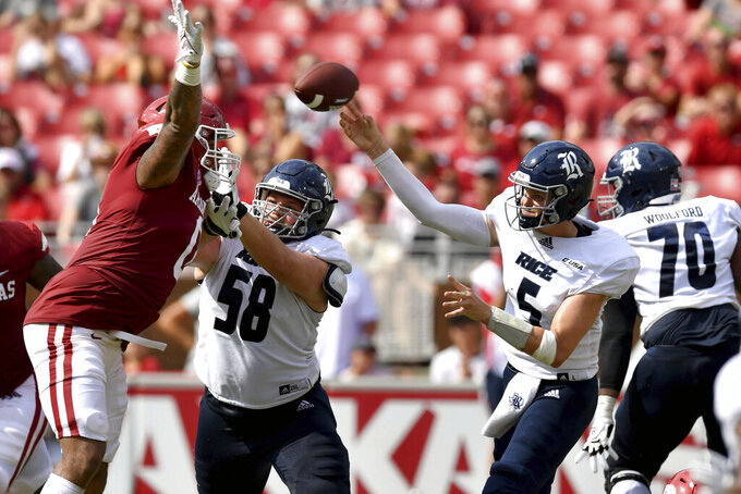 Rice quarterback Wiley Green (5) throws an interception as Arkansas defender AJ Green (0) gets around offensive lineman Shea Baker (58) during the second half of an NCAA college football game Saturday, Sept. 4, 2021, in Fayetteville, Ark. (AP Photo/Michael Woods)