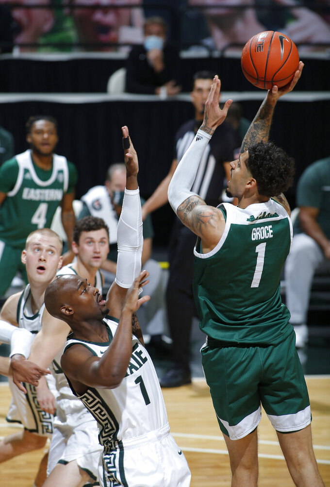 Eastern Michigan's Ty Groce, right, shoots over Michigan State's Joshua Langford during the first half of an NCAA college basketball game Wednesday, Nov. 25, 2020, in East Lansing, Mich. (AP Photo/Al Goldis)