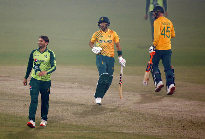 South Africa's Reeza Hendricks, center, and Heinrich Klaasen, right, runs between the wicket while Pakistan's Usman Qadir watches during the 1st Twenty20 cricket match between Pakistan and South Africa at the Gaddafi Stadium, in Lahore, Pakistan, Thursday, Feb. 11, 2021. (AP Photo/K.M. Chaudary)