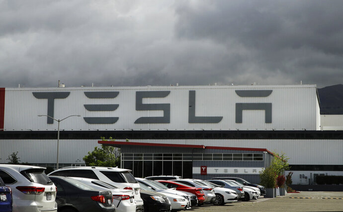 FILE - This Tuesday, May 12, 2020, file photo shows the Tesla plant, in Fremont, Calif. Some Tesla workers and labor activists say the company is threatening to fire employees who haven't returned to the company's California factory since it reopened because they're afraid of catching the coronavirus. (AP Photo/Ben Margot, File)
