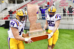 "LSU players Tory Carter (44) and Nick Storz (85) carry ""The Boot"" trophy off the field after defeating Arkansas 27-24 in an NCAA college football game Saturday, Nov. 21, 2020, in Fayetteville, Ark. (AP Photo/Michael Woods)"