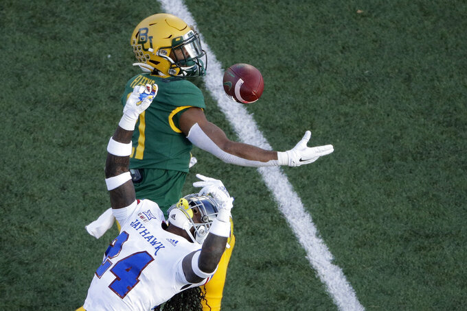 Kansas safety Ricky Thomas, bottom, intercepts a pass intended for Baylor wide receiver Josh Fleeks, top, during the first half of an NCAA college football game Saturday, Nov. 30, 2019, in Lawrence, Kan. (AP Photo/Charlie Riedel)