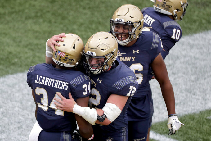 Navy fullback Jamale Carothers (34) is congratulated by center Ford Higgins (72) and offensive tackle Mattie Conlon (56) after scoring on a run against Tulane during the first half of an NCAA college football game, Saturday, Oct. 26, 2019, in Annapolis. (AP Photo/Julio Cortez)