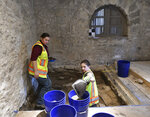 Tiffany Lindley, left, and Tyler Brown remove soil for an archaeological dig in the Long Barrack on the Alamo grounds on Tuesday, Aug. 13, 2019. (Billy Calzada/The San Antonio Express-News via AP)