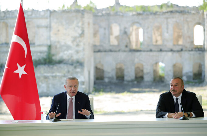 """Azerbaijani President Ilham Aliyev, right, and Turkey's President Recep Tayyip Erdogan speak after they have signed """" the Shusha Declaration """" in Shusha, in Nagorno-Karabakh, Azerbaijan, Tuesday, June 15, 2021. Shusha, is a culturally revered city that Azerbaijan liberated from Armenian forces in last autumn's war. Shusha, a center of Azerbaijani Turkish culture for centuries, came under Armenian control in 1992 in fighting over the separatist Nagorno-Karabakh region.(Turkish Presidency via AP, Pool)"""