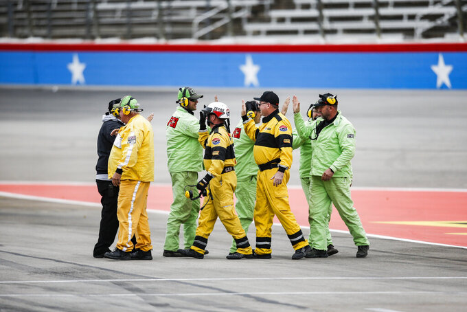 Members of the race safety crews high five each other before a NASCAR auto race at Texas Motor Speedway, Saturday, March 30, 2019, in Fort Worth, Texas. (AP Photo/Brandon Wade)
