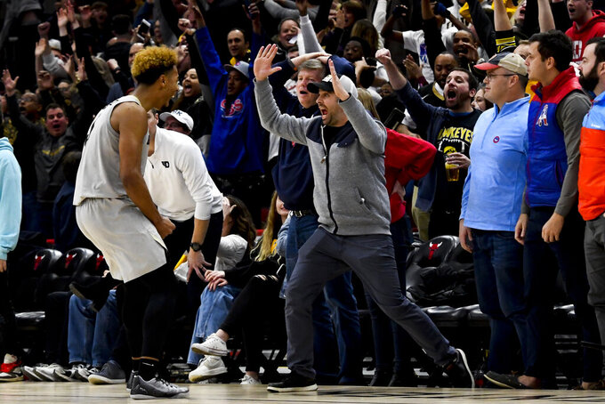 Colorado guard D'Shawn Schwartz, left, reacts with fans after sinking the game-winning shot in overtime of an NCAA college basketball game against Dayton, Saturday, Dec. 21, 2019, in Chicago. Colorado won 78-76. (AP Photo/Matt Marton)