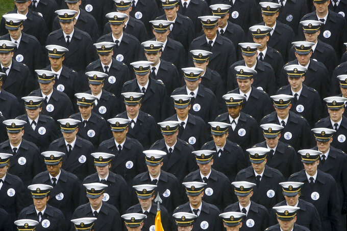 """FILE - In this Dec. 14, 2019 file photo, Navy midshipmen march onto field ahead of an NCAA college football game between the Army and the Navy in Philadelphia. A military investigation finds that hand gestures used by cadets and midshipmen during the Army-Navy game broadcast had nothing to do with white supremacy. The investigation, which included interviews and background checks, determined that two freshmen were taking part in a """"sophomoric"""" game that had """"no racist intent.""""   (AP Photo/Matt Rourke, File)"""
