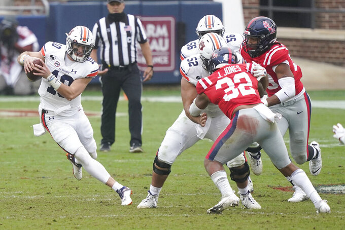 Auburn quarterback Bo Nix (10) follows a block by his offensive lineman Nick Brahms (52) on Mississippi linebacker Jacquez Jones (32) for short yardage during the second half of an NCAA college football game in Oxford, Miss., Saturday, Oct. 24, 2020.  (AP Photo/Rogelio V. Solis)