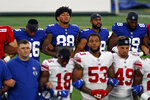 New York Giants tight end Evan Engram (88) and Saquon Barkley (26) stand with linked arms with teammates to make a social injustice statement prior to their scrimmage at the NFL football team's training camp in East Rutherford, N.J., Friday, Aug. 28, 2020. (AP Photo/Adam Hunger)