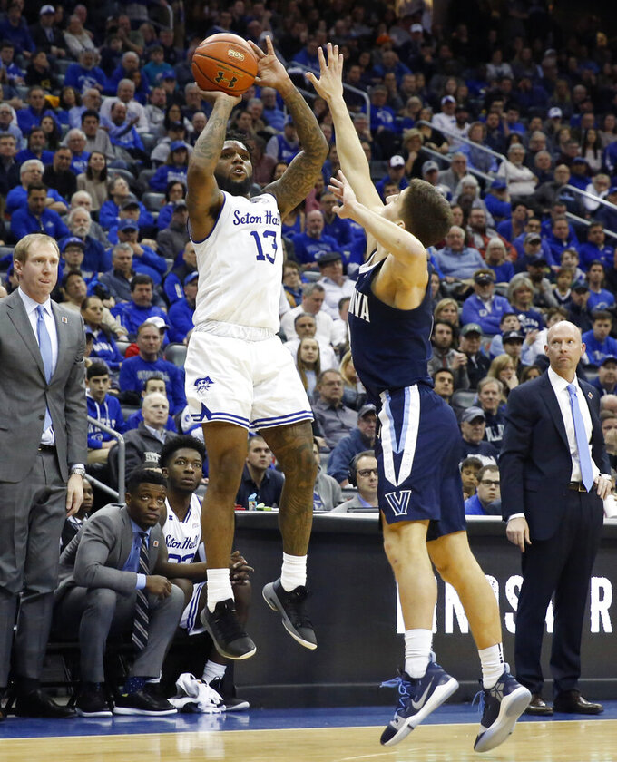 Villanova guard Collin Gillespie, right, defends as Seton Hall guard Myles Powell (13) shoots a 3-pointer during the second half of an NCAA college basketball game, Saturday, March 9, 2019, in Newark, N.J. Seton Hall defeated Villanova 79-75. (AP Photo/Kathy Willens)
