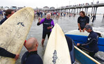 FILE - In this Oct. 3, 2010, file photo, Rev. Christian Mondor, offers a prayer to surfers during the Blessing of the Waves ceremony at the pier in Huntington Beach, Calif. California Gov. Jerry Brown announced Monday, Aug. 20, 2018 that he signed a bill making surfing the official state sport. (AP Photo/Richard Vogel, File)