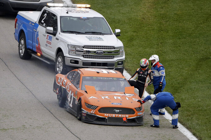 Daniel Suarez is helped from his car after being involved in an accident during a NASCAR Cup Series auto race at Kansas Speedway in Kansas City, Kan. Sunday, Oct. 20, 2019. (AP Photo/Charlie Riedel)
