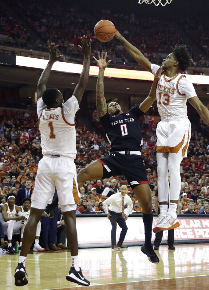 Texas Tech guard Kyler Edwards (0) is blocked by Texas guard Jase Febres (13) as he tries to score during the first half of an NCAA college basketball game, Saturday, Feb. 8, 2020, in Austin, Texas. (AP Photo/Eric Gay)
