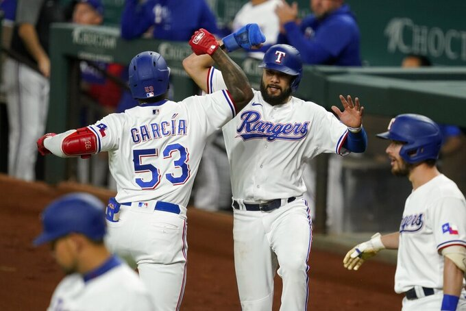Texas Rangers' Adolis Garcia (53) and Isiah Kiner-Falefa, center right, celebrate Garcia's two-run home run that scored Kiner-Falefa against the Houston Astros during the the third inning of a baseball game in Arlington, Texas, Tuesday, Sept. 14, 2021. In the foreground are Rangers' Nathaniel Lowe, left, and Nick Solak. (AP Photo/Tony Gutierrez)