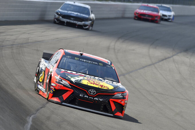 Martin Truex Jr. (19) drives through Turn 1 during a NASCAR Cup Series auto race, Sunday, July 28, 2019, in Long Pond, Pa. Denny Hamlin won the race. (AP Photo/Derik Hamilton)
