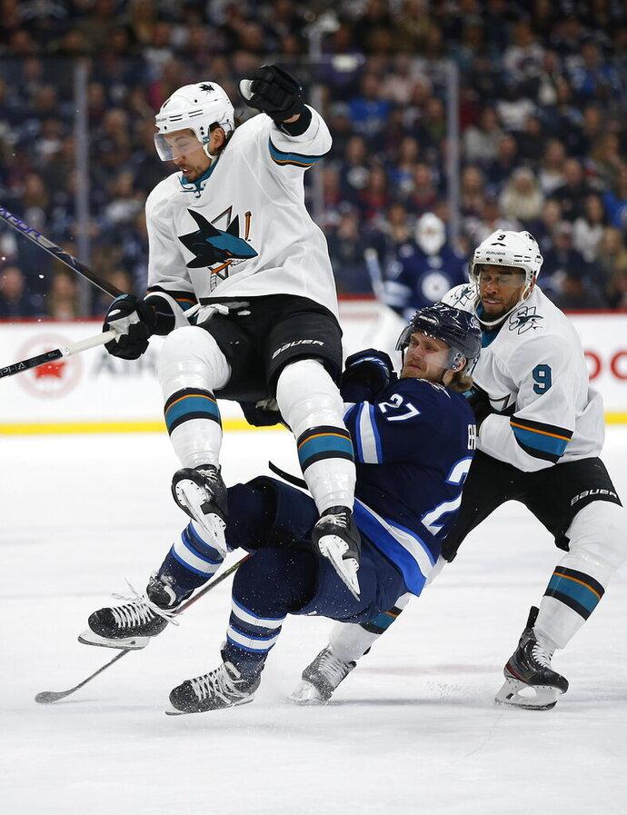 Winnipeg Jets' Nikolaj Ehlers (27) and San Jose Sharks' Brenden Dillon (4) collide as Sharks' Evander Kane (9) skates by during the second period of an NHL hockey game Friday, Feb. 14, 2020, in Winnipeg, Manitoba. (John Woods/The Canadian Press via AP)
