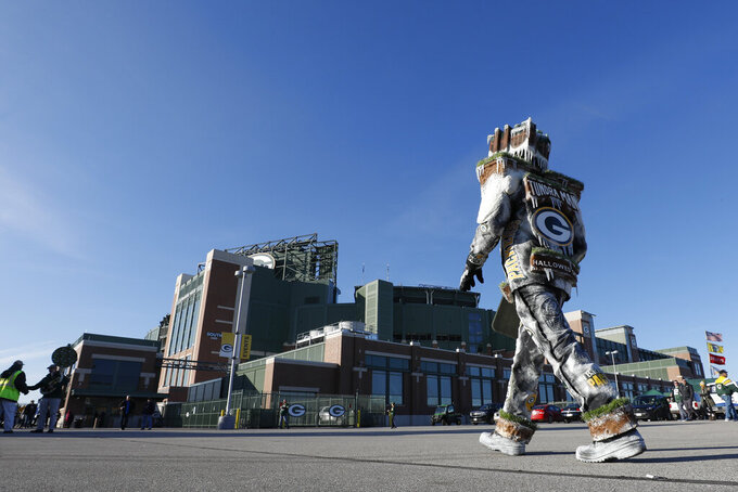 A fan walks outside Lambeau Field before an NFL football game between the Green Bay Packers and the Detroit Lions Monday, Oct. 14, 2019, in Green Bay, Wis. (AP Photo/Jeffrey Phelps)
