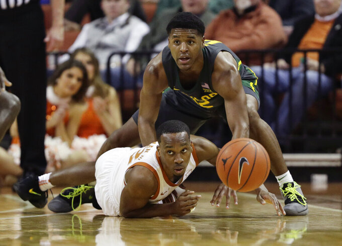 Texas guard Matt Coleman III, bottom, and Baylor guard Jared Butler, right, chase the ball during the first half of an NCAA college basketball game, Monday, Feb. 10, 2020, in Austin, Texas. (AP Photo/Eric Gay)