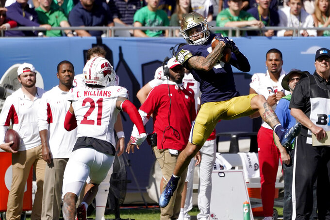 Notre Dame wide receiver Braden Lenzy catches a pass as Wisconsin cornerback Caesar Williams comes up to defend during the first half of an NCAA college football game Saturday, Sept. 25, 2021, in Chicago. (AP Photo/Charles Rex Arbogast)