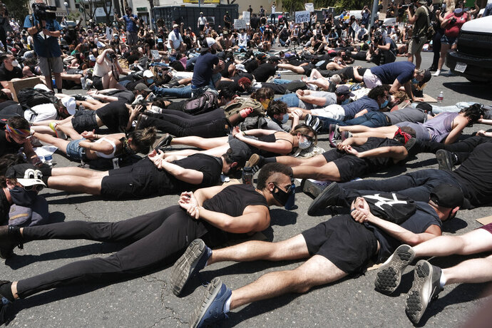 LGBTQ community members join Black Lives Matter demonstrators lie face down depicting George Floyd during his detention by police, blocking an intersection in protest over Floyd's death, in West Hollywood, Calif., on Wednesday, June 3, 2020.  Floyd, an African American, died on May 25 after a white Minneapolis police officer pressed a knee into his neck for several minutes even after he stopped moving and pleading for air. (AP Photo/Richard Vogel)