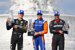 From left to right, Marcus Ericsson, of Sweden, third place finisher; Scott Dixon, of New Zealand, first place; and Will Power (12), of Australia, second place, celebrate after with their trophies after the second race of the IndyCar Detroit Grand Prix auto racing doubleheader in Detroit, Sunday, June 2, 2019. (AP Photo/Paul Sancya)