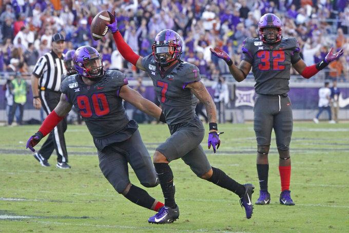 FILE - In this Oct. 26, 2019, file photo, TCU safety Trevon Moehrig (7) celebrates his interception with teammates Ross Blacklock (90) and Ochaun Mathis (32) in the second half of an NCAA college football game, in Fort Worth, Texas. Moehrig was selected to The Associated Press All-Big 12 Conference team, Friday, Dec. 13, 2019. (AP Photo/Louis DeLuca, File)