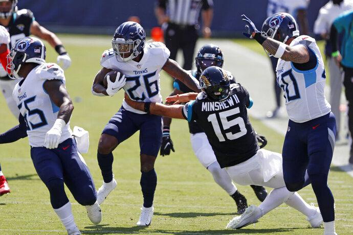 Tennessee Titans cornerback Kristian Fulton (26) runs back an interception as Jacksonville Jaguars quarterback Gardner Minshew (15) tries to tackle him in the first half of an NFL football game Sunday, Sept. 20, 2020, in Nashville, Tenn. (AP Photo/Wade Payne)