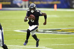 Baltimore Ravens quarterback Lamar Jackson runs with the ball against the Tennessee Titans during the first half of an NFL football game, Sunday, Nov. 22, 2020, in Baltimore. (AP Photo/Gail Burton)