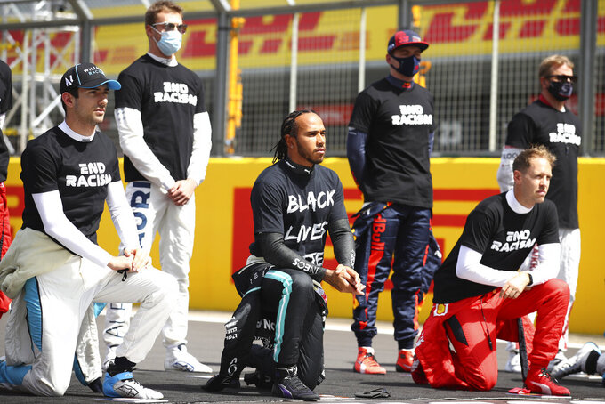 Mercedes driver Lewis Hamilton of Britain, center and other drivers rivers kneel during the anti-racism demonstration ahead of the British Formula One Grand Prix at the Silverstone racetrack, Silverstone, England, Sunday, Aug. 2, 2020. (Bryn Lennon/Pool via AP)