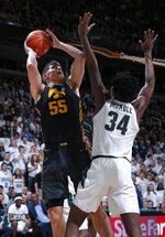 Iowa's Luka Garza, left, shoots against Michigan State's Julius Marble (34) during the first half of an NCAA college basketball game, Tuesday, Feb. 25, 2020, in East Lansing, Mich. (AP Photo/Al Goldis)