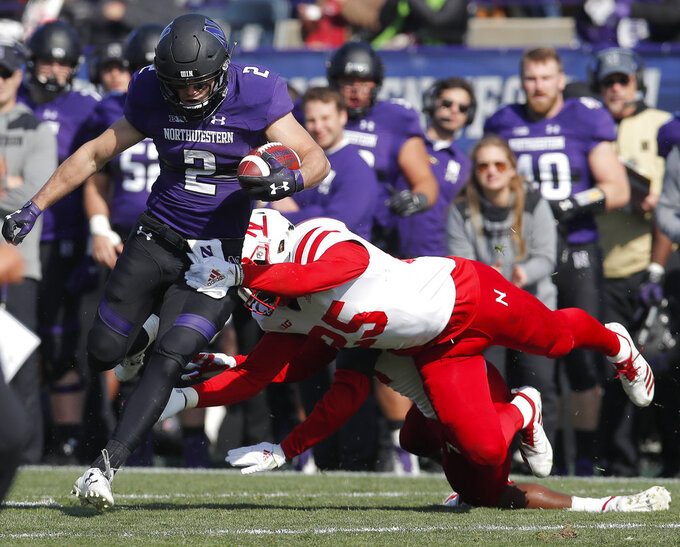 Northwestern's Flynn Nagel, left, tries to break a tackle by Nebraska's Antonio Reed during the second half of an NCAA college football game Saturday, Oct. 13, 2018, in Evanston, Ill. (AP Photo/Jim Young)