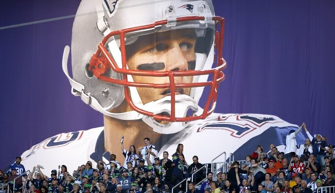 FILE - In this Feb. 1, 2015, file photo, fans cheer under a banner of New England Patriots quarterback Tom Brady (12) before the NFL Super Bowl XLIX football game between the Seattle Seahawks and the New England Patriots, in Glendale, Ariz. (AP Photo/Matt Slocum, File)