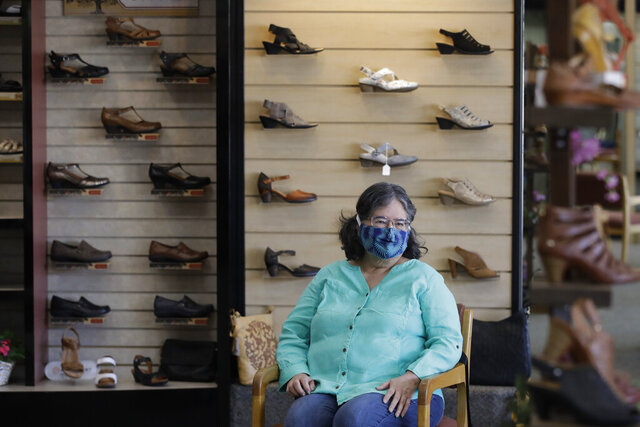 Yvonne Wright shops for shoes at Brown's Shoe Fit Co. Wednesday, May 20, 2020, in Visalia, Calif. Tulare County's board of supervisors voted 3-2 Tuesday to move further into the state's four-stage reopening plan than is allowed. That means nearly all businesses and churches could reopen, though county officials said businesses should adhere to state guidelines on social distancing and other health measures. (AP Photo/Marcio Jose Sanchez)