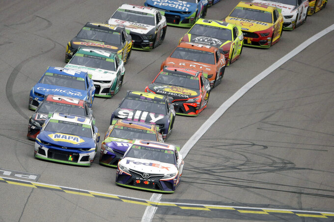 Denny Hamlin, front right, leads the pack out of the final caution before winning a NASCAR Cup Series auto race at Kansas Speedway in Kansas City, Kan. Sunday, Oct. 20, 2019. (AP Photo/Charlie Riedel)